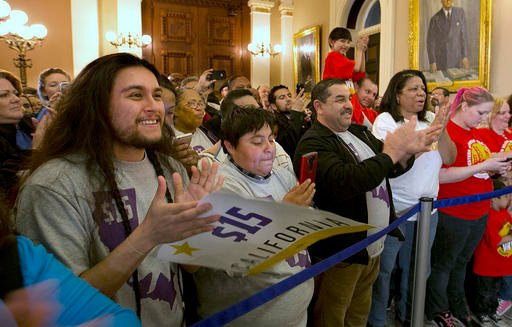 Supporters of a bill to raise California's minimum wage, celebrate outside the state Senate Chamber after the measure was approved by the Senate Thursday, March 31, 2016, in Sacramento, Calif.