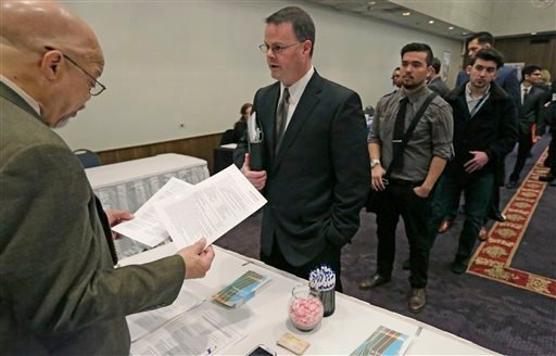 FILE - In this April 22, 2015 file photo, Ralph Logan, general manager of Microtrain, left, speaks with James Smith who is seeking employment during a National Career Fairs job fair in Chicago.
