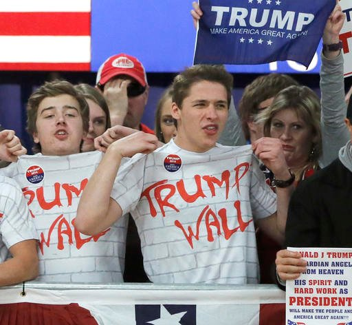 Supporters of Republican presidential candidate, Donald Trump, chant, Build That Wall, before a town hall Saturday, April 2, 2016, in Rothschild, Wis. (AP Photo/Charles Rex Arbogast)