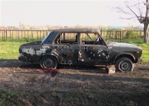 In this image from TV, a car destroyed with blood showing in the aftermath after heavy fighting erupted in Terter, Azerbaijan, Saturday April 2, 2016, between Armenian and Azerbaijani forces over the separatist region of Nagorno-Karabakh. Russia expressed