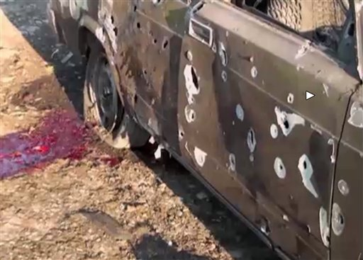 In this image from TV, a car lays destroyed with blood showing in the aftermath after heavy fighting erupted in Terter, Azerbaijan, Saturday April 2, 2016, between Armenian and Azerbaijani forces over the separatist region of Nagorno-Karabakh. Russia expr