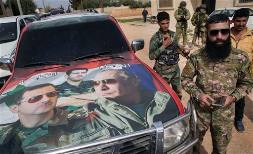In this March 2, 2016, file photo, Syrian solders and Russian solders, who escort a group of journalists in the background, stand near a car covered by collage showing photos of faces of Russian President Vladimir Putin, right, Syrian President Bashar As