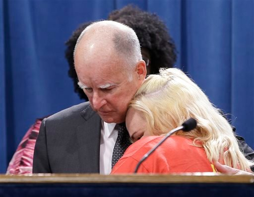 March 28, 2016 photo, Gov. Jerry Brown is hugged by Holly Dias, a Burger King employee who praised Brown's announcement of proposed legislation to increase the state's minimum wage to $15 per hour by 2022 in Sacramento, Calif. (AP Photo/Rich Pedroncelli)