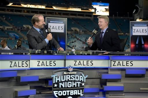 In this Nov. 19, 2015, file photo, Thursday Night Football sportscasters Bill Cowher, left, and Phil Simms broadcast from the set on the field before an NFL football game.