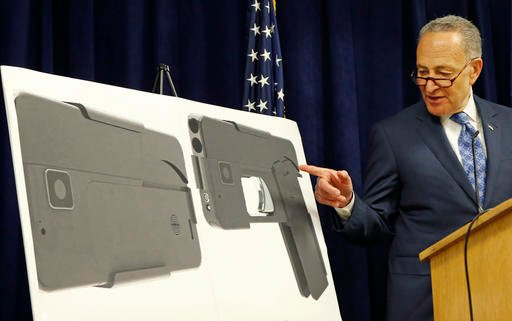 U.S. Sen Charles Schumer, (D-New York), points to photographs of what appears to be a cell phone, but is actually a handgun, during a press conference in his office, Monday, April 4, 2016, in New York.