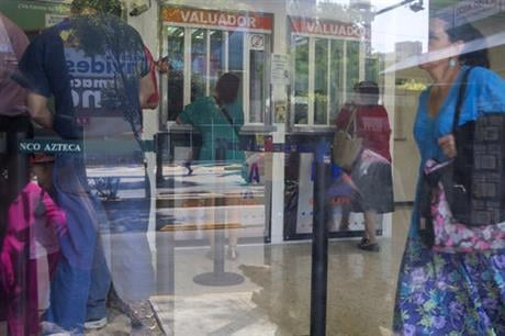 Customers are seen inside a business offering money transfers and loans, in Mexico City, Tuesday, April 5, 2016. U.S. Republican Presidential frontrunner Donald Trump is threatening to block billions of dollars in U.S. remittances to force Mexico to pay f