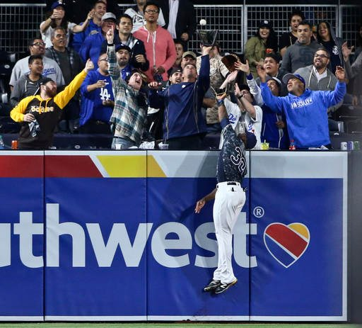 San Diego Padres left fielder Jabari Blash leaps at the wall but cannot catch a home run hit by Los Angeles Dodgers' Yasiel Puig during the eighth inning of a baseball game Wednesday, April 6, 2016, in San Diego.