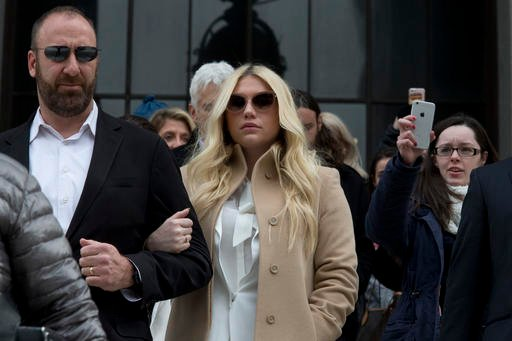 In this Feb. 19, 2016 file photo, pop star Kesha, center, leaves Supreme court in New York.