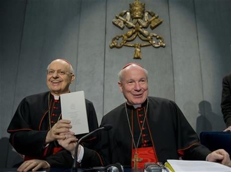 Cardinals Lorenzo Baldisseri, left, and Christoph Schoenborn show a copy of the post-synodal apostolic exhortation ' Amoris Laetitia ' (The Joy of Love) during a press conference at the Vatican, Friday, April 8, 2016.  AP