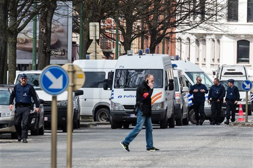 Police secure an area during a house search in the Etterbeek neighborhood in Brussels on Saturday April 9, 2016. The arrest Friday of six men suspected of links to the Brussels bombings, including the last known fugitive in last year's Paris attacks, rais