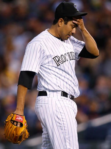 Colorado Rockies starting pitcher Jorge De La Rosa reacts after giving up a three-run home run to San Diego Padres' Matt Kemp in the fourth inning of a baseball game Saturday, April 9, 2016, in Denver. (AP Photo/David Zalubowski)