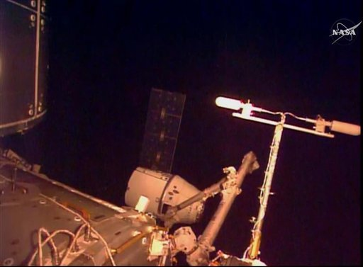 In this frame taken from video from NASA TV, the SpaceX Dragon cargo ship is captured by a robot arm from the International Space Station, Sunday April 10, 2016. A SpaceX Dragon cargo ship arrived at the International Space Station on Sunday, two days aft