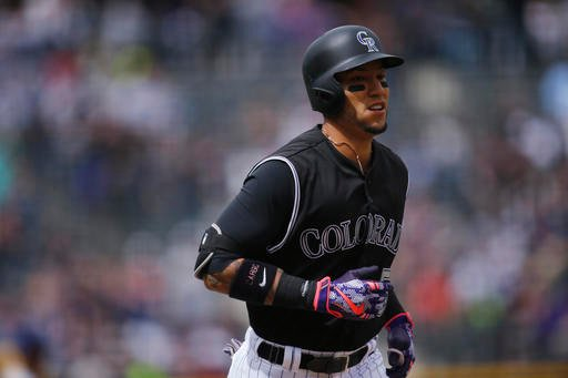 Colorado Rockies' Carlos Gonzalez circles the bases after hitting a solo home run off San Diego Padres starting pitcher James Shields in the first inning of a baseball game Sunday, April 10, 2016, in Denver. (AP Photo/David Zalubowski)