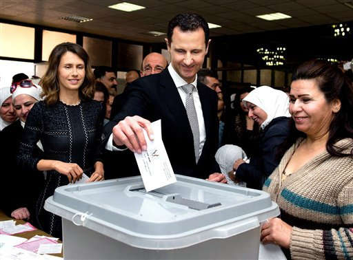 This photo released on the official Facebook page of Syrian Presidency, shows Syrian President Bashar Assad casting his ballot in the parliamentary elections, as his wife Asma, left, stands next to him, in Damascus, Syria, Wednesday, April 13, 2016. Syria