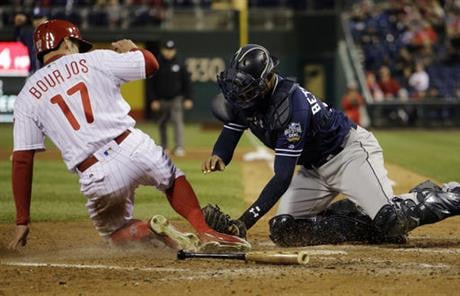 Philadelphia Phillies' Peter Bourjos, left, is tagged out by San Diego Padres catcher Christian Bethancourt after trying to score on a fielding error by shortstop Alexi Amarista during the fourth inning of a baseball game, Wednesday, April 13, 2016, in Ph