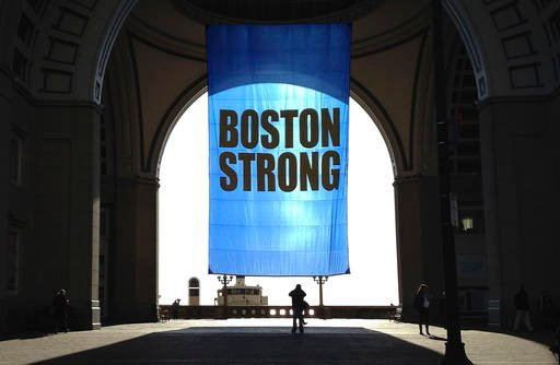 People stop to photograph a Boston Strong banner hanging at Rowes Wharf on Friday, April 15, 2016, in Boston, to commemorate the third anniversary of the Boston Marathon bombings.