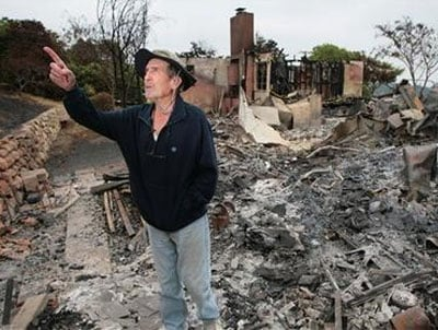 Robert Pratini, 88, points to his burned avocado trees outside his destroyed home in Santa Barbara, Calif., on Sunday, May 10, 2009. (AP Photo/Eric Parsons)
