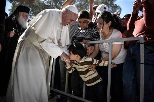 In this photo released by Greek Prime Minister's office on Saturday, April 16, 2016, a child kisses the hand of Pope Francis, during a visit at the Moria refugee camp on the island of Lesbos, Greece.