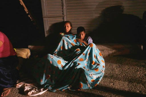 Residents sit in the street covered with blankets in the Pacific coastal town of Pedernales, Ecuador, Sunday, April 17, 2016. The strongest earthquake to hit Ecuador in decades flattened buildings and buckled highways along its Pacific coast, sending the