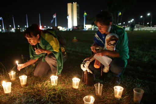 Anti-government protesters light candles outside Congress where lawmakers debate whether to oust the Brazil's President Dilma Rousseff in Brasilia, Brazil, Saturday, April 16, 2016. Sunday's vote will determine whether the impeachment proceeds to the Sena