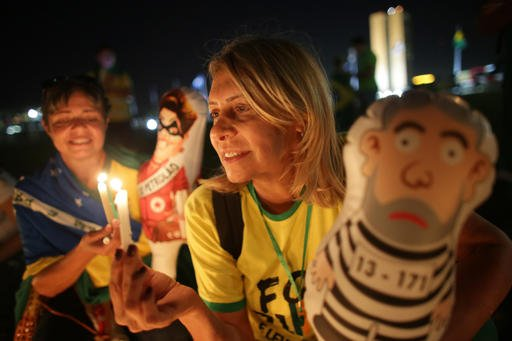 An anti-government demonstrators holds a candle and caricature of Brazil's former President Luiz Inacio Lula da Silva in prison garb, outside Congress where lawmakers debate whether to oust his protege, Brazil's President Dilma Rousseff, in Brasilia, Braz