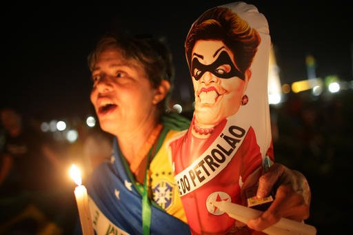 "An Anti-government demonstrator holds a caricature of Brazil's President Dilma Rousseff wearing a bandit mask and sash that reads in Portuguese ""Big oil"" outside Congress where lawmakers debate whether to oust the Brazil's President Dilma Rousseff in Bras"