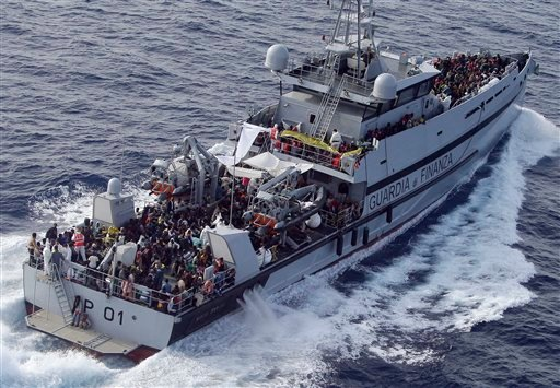In this Thursday, May 14, 2015 file photo, rescued migrants are seen aboard MP01 ship of the Italian border police in the Mediterranean Sea, heading to the Island of Lampedusa, southern Italy. On upcoming April 18, 2016, it will be one year since some 800