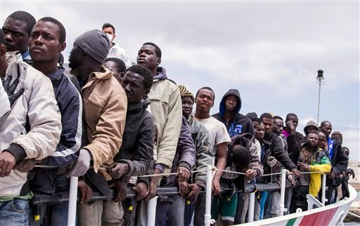 In this Sunday, May 31, 2015 file photo, migrants wait to disembark from the Italian Coast Guard ship Peluso, onto the tiny Italian island of Lampedusa. On upcoming April 18, 2016, it will be one year since some 800 migrants died when an overcrowded ship