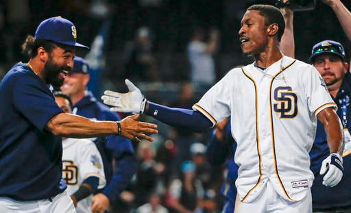 San Diego Padres' Melvin Upton Jr., right, slaps hands teammate Matt Kemp as the celebrate Upton Jr.'s two-run homer in the 14th inning that gave the Padres a 5-3 victory over the Arizona Diamondbacks in a baseball game Saturday, April 16, 2016, in San Di