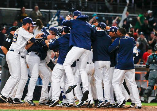 San Diego Padres' surround Melvin Upton Jr. as they celebrate his two run-homer in the 14th inning to give the Padres a 5-3 victory over the Arizona Diamondbacks in a baseball game Saturday, April 16, 2016, in San Diego. (AP Photo/Lenny Ignelzi)