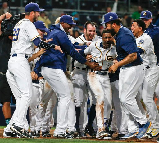 San Diego Padres' Melvin Upton Jr. is mobbed by teammates as they celebrate his two run-homer in the 14th inning that gave the Padres a 5-3 victory over the Arizona Diamondbacks in a baseball game Saturday, April 16, 2016, in San Diego. (AP Photo/Lenny Ig