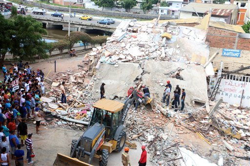 Rescue workers search a collapsed building in Manta, Ecuador, Sunday April 17, 2016. A powerful, 7.8-magnitude earthquake shook Ecuador's central coast on Saturday, killing hundreds and spreading panic as it collapsed homes.(AP Photo/Patricio Ramos)