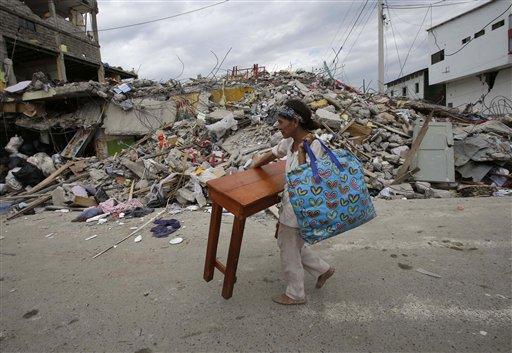 A woman carries a table through the street after an earthquake in Pedernales, Ecuador, Sunday, April 17, 2016. (AP Photo/Dolores Ochoa)
