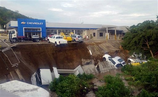 Vehicles from a car dealership hang on a precipice caused by an earthquake induced landslide in Portoviejo, Ecuador, Sunday, April 17, 2016. (AP Photo/Juan Fernando Molina)