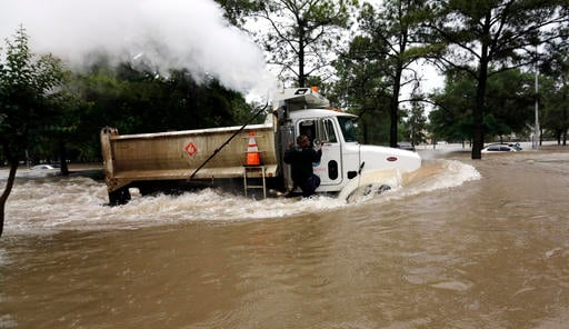 A man rides on the outside of a dump truck through floodwaters Monday, April 18, 2016, in Houston. (AP Photo/David J. Phillip)
