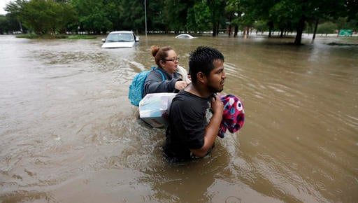 Margarita Uribe, left, and her husband, Juan Juarez, wade through floodwaters as they evacuate their flooded apartment complex Monday, April 18, 2016, in Houston. (AP Photo/David J. Phillip)
