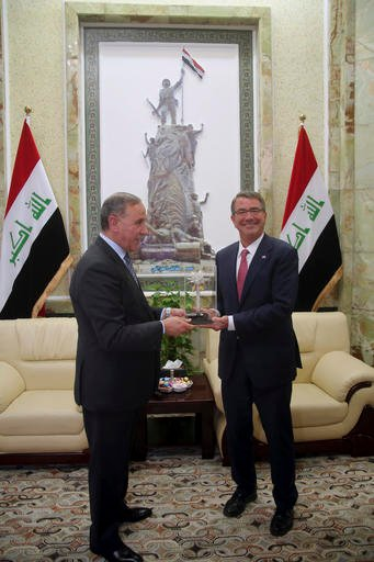 Visiting U.S. Defense Secretary Ash Carter, right, receives a gift from his Iraqi counterpart Khaled al-Obeidi during their meeting at the Ministry of Defense, Baghdad, Iraq, Monday, April 18, 2016. (AP Photo)