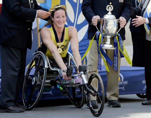 Tatyana McFadden, of Clarksville, Md., receives her victor's wreath and trophy after winning the women's wheelchair division of the 120th Boston Marathon on Monday, April 18, 2016, in Boston.