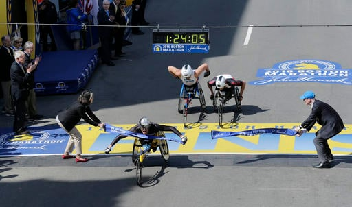 Marcel Hug, of Switzerland, breaks the tape ahead of Kurt Fearnley, of Australia, center, and Ernst Van Dyk, of South Africa, in the wheelchair division of the 120th Boston Marathon on Monday, April 18, 2016, in Boston.