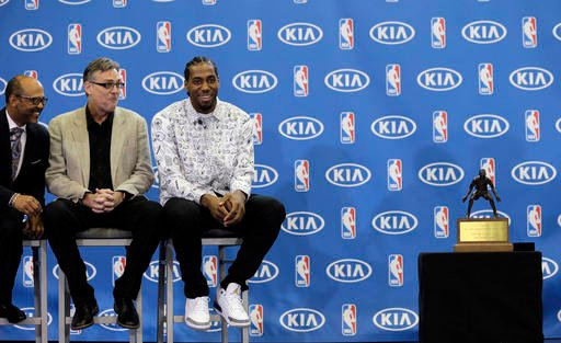 San Antonio Spurs' Kawhi Leonard, right, waits to receive his trophy during a news conference where he was named the NBA defensive player of the year, Monday, April 18, 2016, in Austin, Texas.