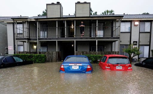 A resident looks out from the second floor as floodwaters surround his apartment complex Monday, April 18, 2016, in Houston.
