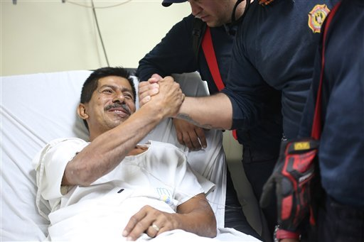 Pablo Rafael Cordova CaÒizares shakes hands with one of the Colombian firefighters who rescued him, at the Verdi Cevallos Balda hospital in Portoviejo, Ecuador, Monday, April 18, 2016.