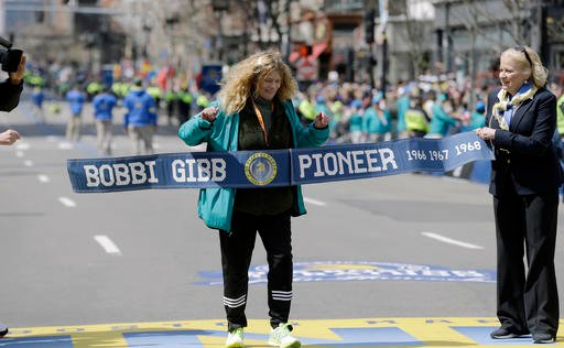 Bobbi Gibb, first woman to run the Boston Marathon in 1966, crosses the finish line for photographers duirng the 120th Boston Marathon on Monday, April 18, 2016, in Boston.