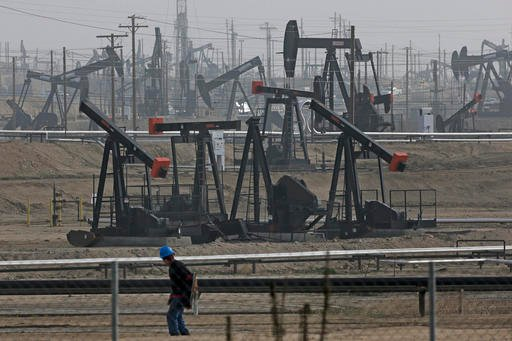 In this Jan. 16, 2015, file photo, a person walks past pump jacks operating at the Kern River Oil Field in Bakersfield, Calif.