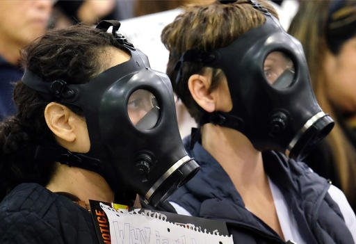 In this Jan. 16, 2016, file photo, protestors wearing gas masks attend a hearing over a gas leak at the southern California Gas Company's Aliso Canyon Storage Facility near the Porter Ranch section of Los Angeles.