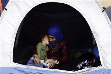 A woman dresses a baby inside a tent at a makeshift camp for migrants and refugees at the northern Greek border point of Idomeni, Greece, Wednesday, April 20, 2016. AP