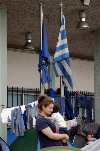 The EU, left, and Greek flags tied together tower over migrants and refugees gathered at a railway station at the northern Greek border point of Idomeni, Greece, Wednesday, April 20, 2016. AP