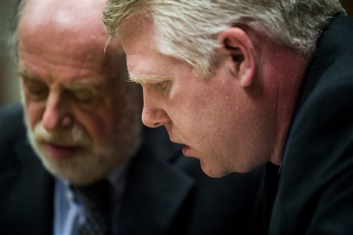 Defense attorney Mark Kriger, left, goes over charges with his client, state Department of Environmental Quality employee Stephen Busch, before an arraignment Wednesday, April 20, 2016, in Flint, Mich. Two state employees facing charges related to the Fli