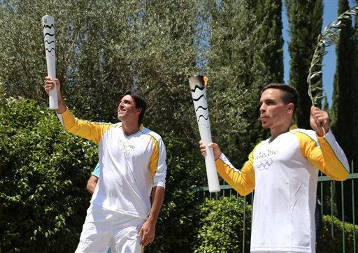 Former Brazilian volleyball player Giovane Gavio, left, and Greek gymnast Eleftherios Petrounias, right, show off their torches with the Olympic flame.