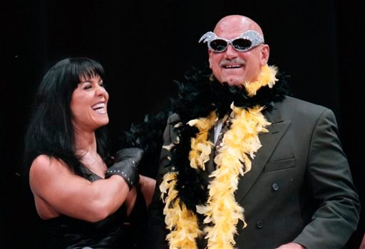 In this July 14, 1999, file photo, Minnesota Gov. Jesse Ventura is adorned with his signature feather boa and glitter sunglasses by professional wrestler Chyna, during a World Wrestling Federation press conference at the Target Center in Minneapolis.